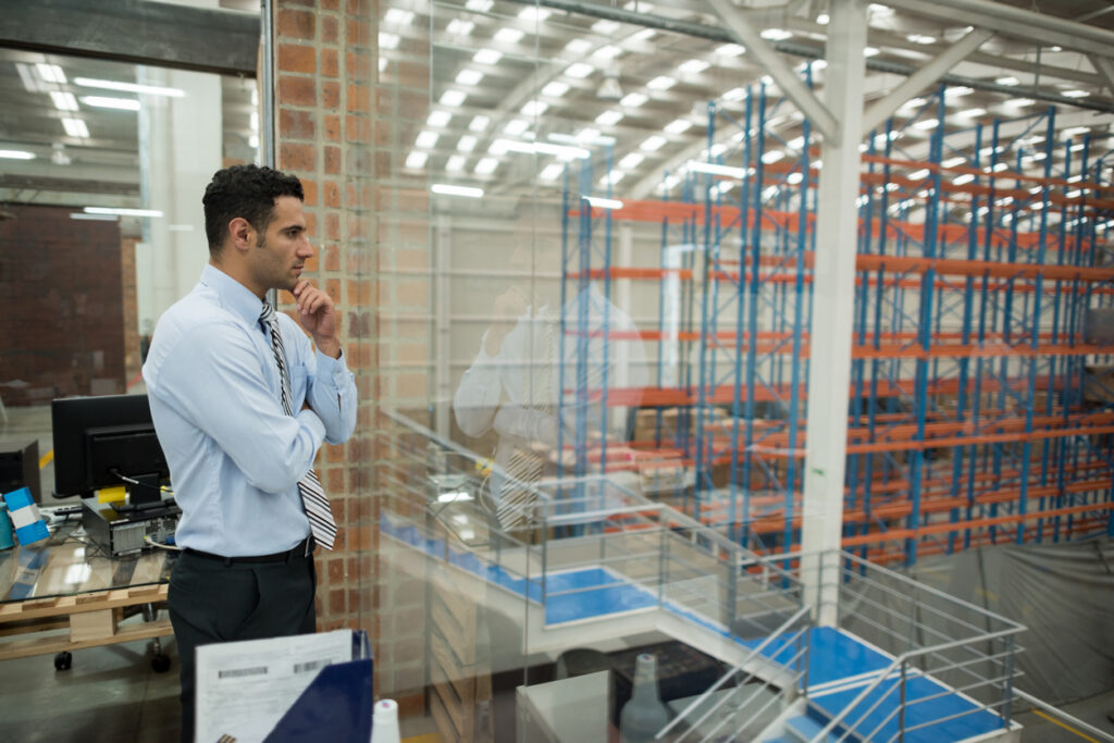 business man in office overlooking warehouse