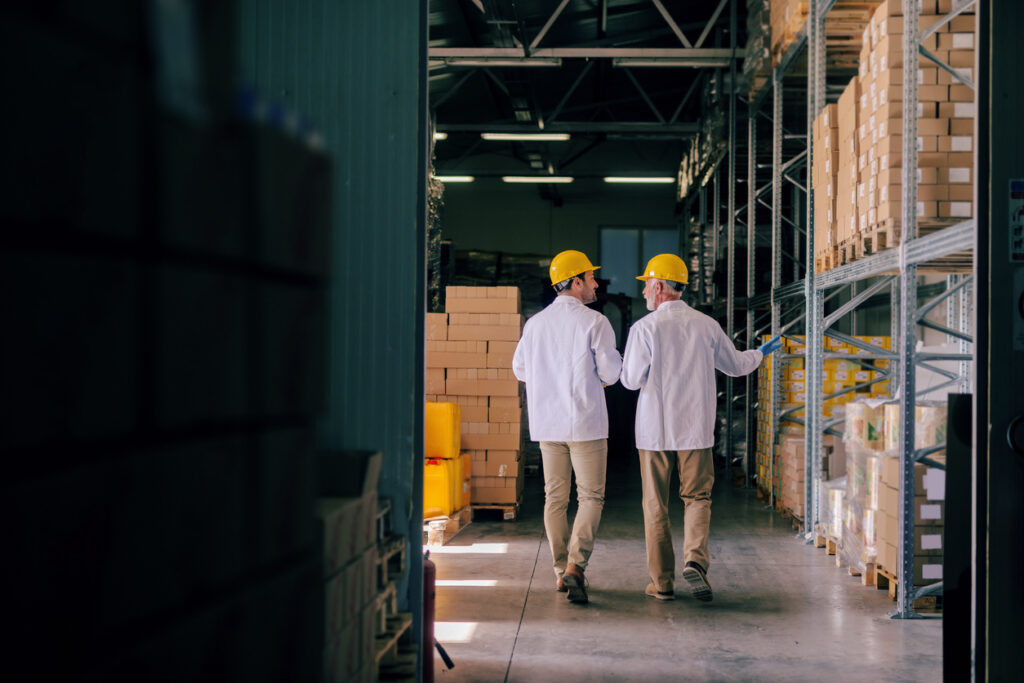 Two warehouse workers walking by rows of steel shelving